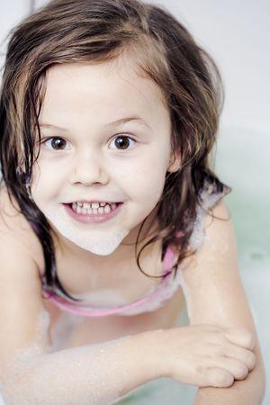 Little girl wearing swimsuit playing i the bathtub photo