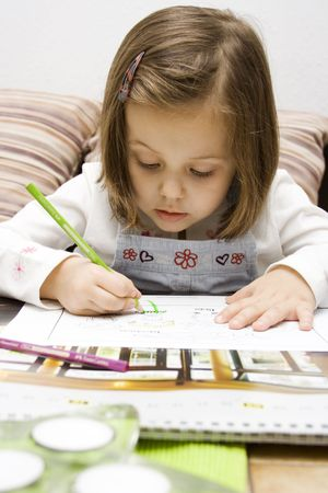 portrait of a 4 years old girl drawing.