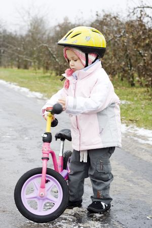 little girl riding on her pink bike photo
