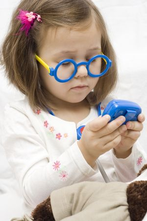 pager: little doctor. 4 years old girl playing with doctor tools