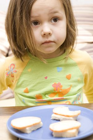 photo of little, cute girl eating a sandwich photo