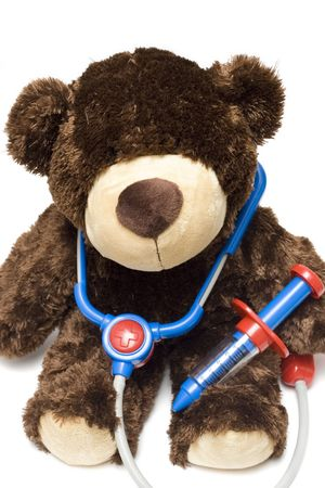 Doctor teddy bear with medical stethoscope and syringe