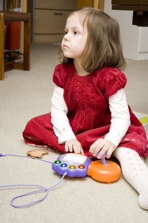 little girl sitting on the floor and playing a video game photo
