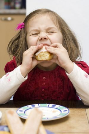 little girl wearing red dress eating a muffin