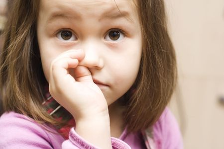 a portrait of little girl with finger in her nose Stock Photo