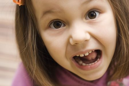 a portrait of little girl making faces photo