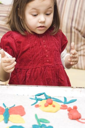 a portrait of little girl playing with dough photo