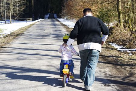 father learning daughter how to ride a bike