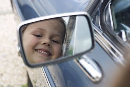 reflection of a little girl in the outside mirror
