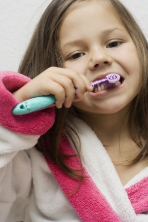 little girl wearing a bathrobe brushing her teeth photo