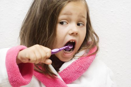 little girl wearing a bathrobe brushing her teeth