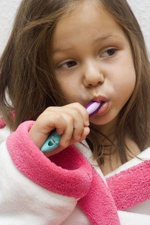 little girl wearing a bathrobe brushing her teeth