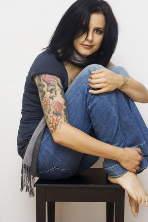 young woman with tattoos sitting on a chair photo