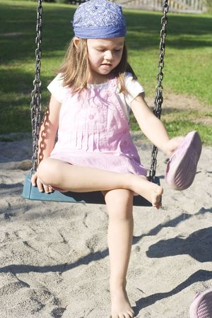 little girl playing on the playground in the rays of sun photo