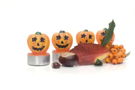 conker: chestnuts, leaves, rowan berries and halloween candles on white