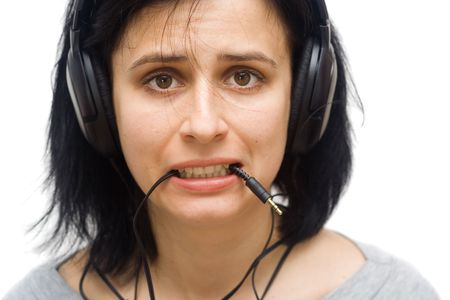 unsatisfied: portrait of an young woman with headphones and jack plug in mouth