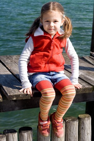 little girl wearing red vest sitting on the pier Stock Photo