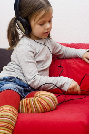 little girl wearing headphones and listening to the music