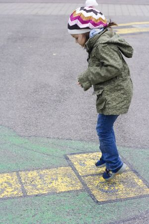 5 years old girl playing a hopscotch photo