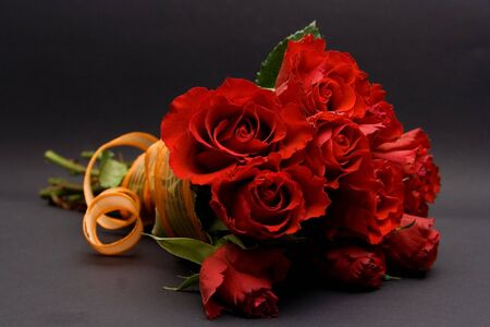 red roses with orange ribbon against the black background photo