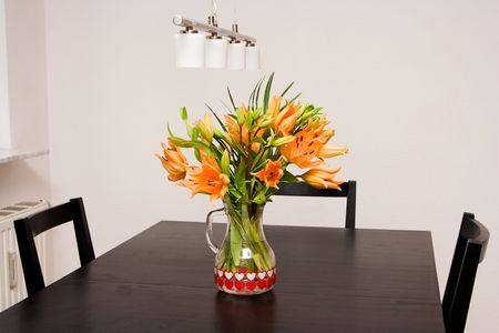 lilies in the vase on the dining table