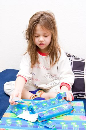 5 year old: girl wearing pyjamas sitting on a bed