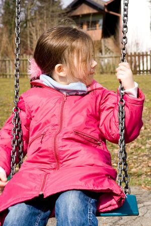 little girl wearing pink jacket having fun on the playground photo
