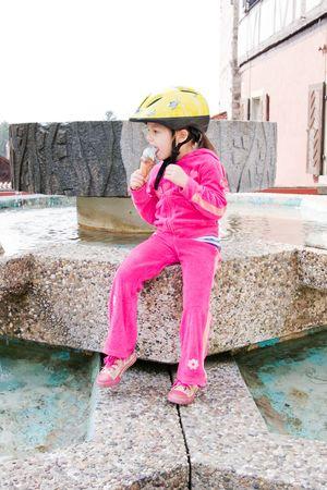 little girl wearing yellow helmet eating an ice cream photo