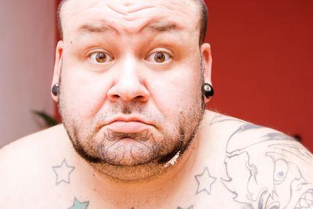 making faces: Ritratto di un uomo con i tatuaggi, rendendo le facce