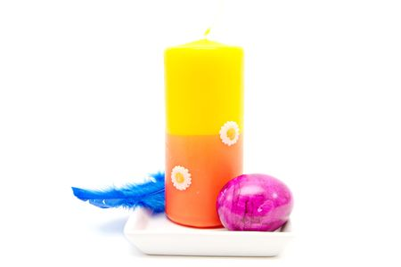 easter candle: easter candle and feather isolated on white