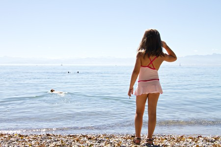 little girl wearing swimsuit looking at the lake Stock Photo