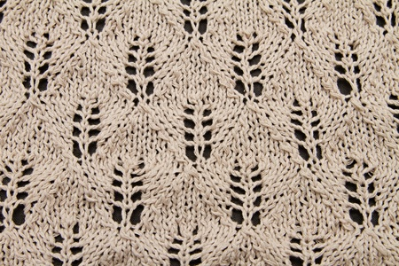 a beige knitted fabric. a close up. photo