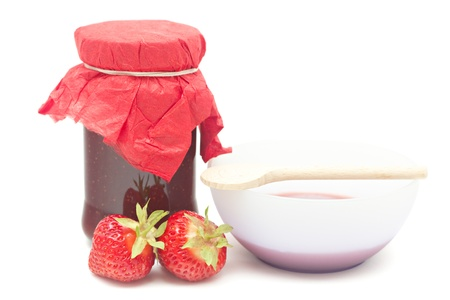 Glass pot with strawberry jam isolated on white  photo