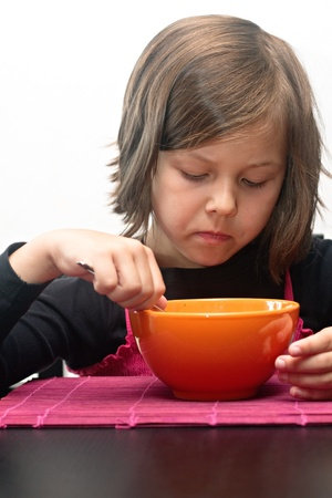 Young girl indoors eating soup from orange bowl