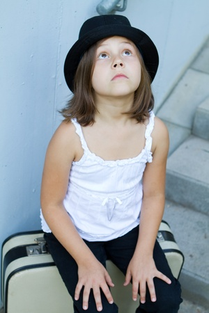 Lonely girl wearing a hat with suitcase
