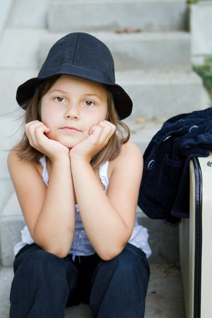 Lonely girl wearing a hat with suitcase Stock Photo - 12171433