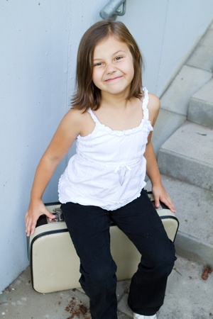A little girl sitting on a  suitcase Stock Photo - 12659765