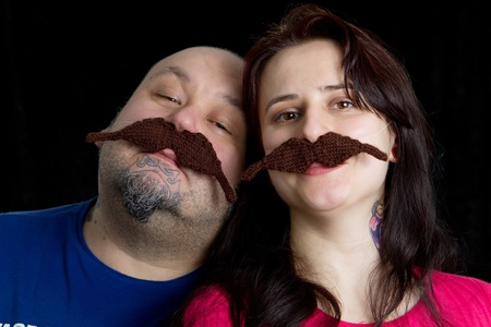 The couple wearing fake moustache against black background