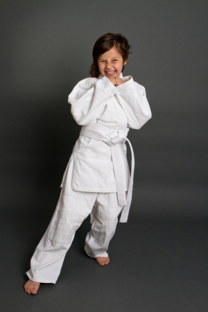 little girl in judo clothing against grey background
