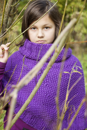 the portrait of a teenage girl wearing purple poncho photo