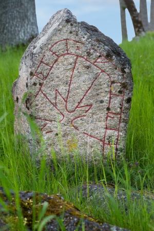 runes: Swedish old rune stone in green grass Stock Photo
