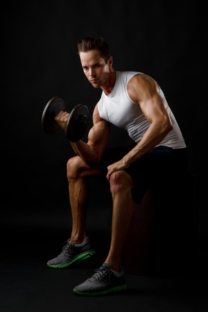 curren: Attractive male doing dumbbell lifts and flexing arm Stock Photo
