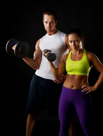 dumbell: Fit young couple doing dumbbell lifts together