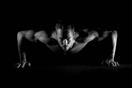 push up: Man with focused eyes doing pushups on black background Stock Photo