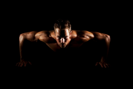 Man with focused eyes doing pushups on black background Stock Photo - 16821254