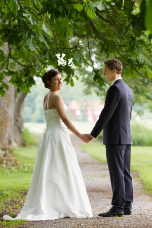 over shoulders: Young couple holding hands and looking back over shoulders at wedding