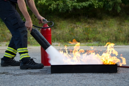 fire safety: Instructor showing how to use a fire extinguisher on a training fire Stock Photo