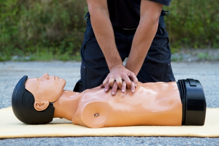 Male instructor showing CPR on training doll photo