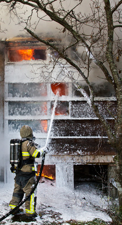 fireman: Fireman using foam to put out fire in house, real world fire Stock Photo