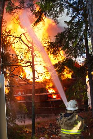 incendio casa: Bombero use agua en casa en el fuego Foto de archivo